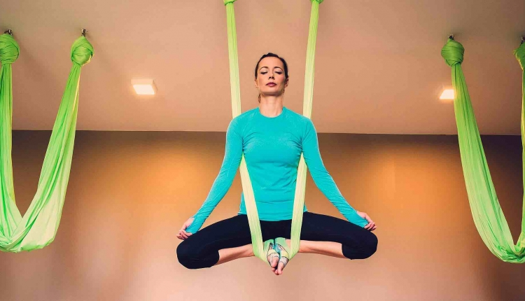 A woman does easy pose hanging from silks