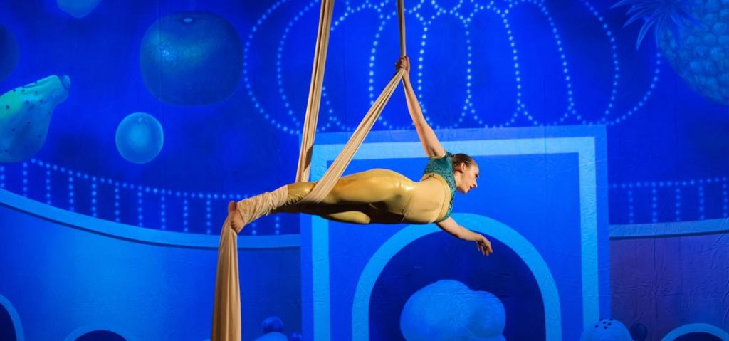 A woman hangs horizontally from silks