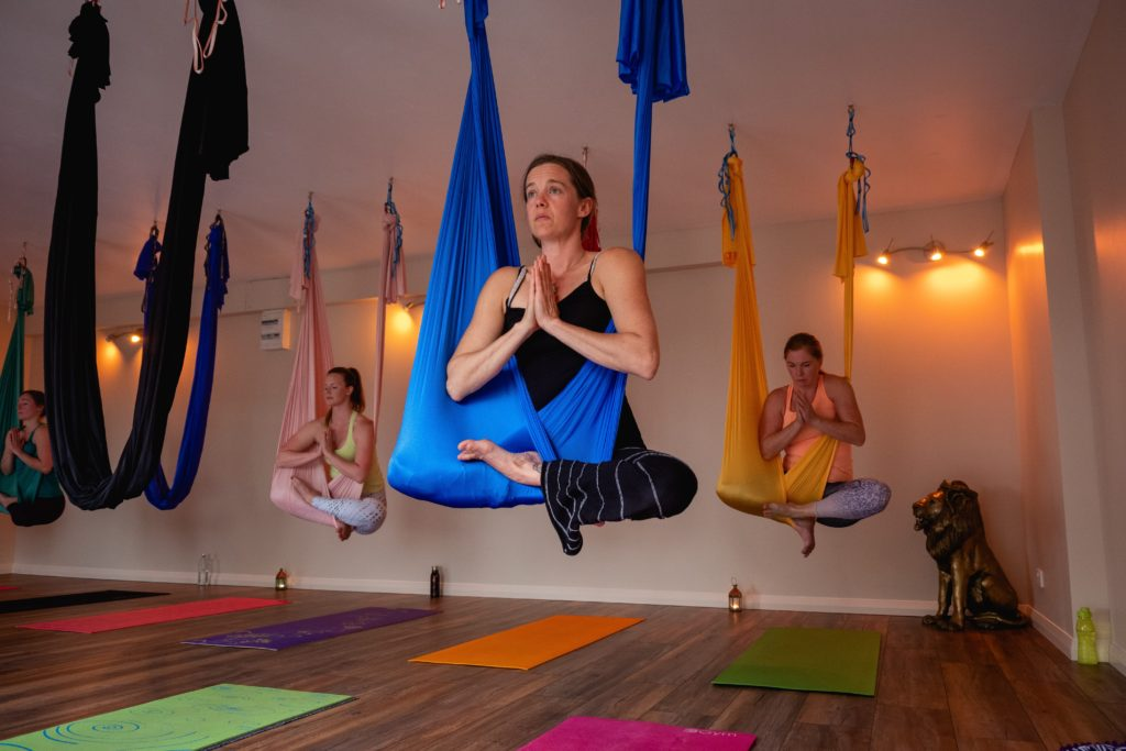 A class full of students in lotus position while hanging from silks