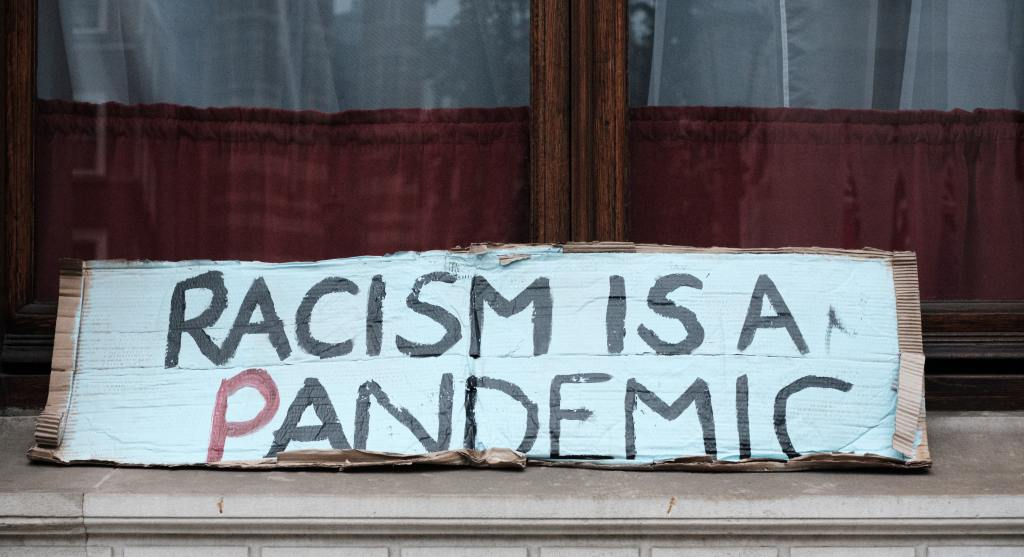 Protest sign reading RACISM IS A PANDEMIC