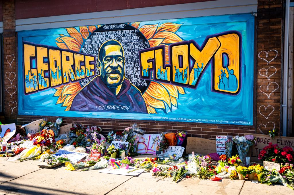 Mural depicting George Floyd with flowers and tributes
