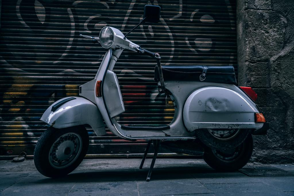 A silver moped parked in front of a garage door covered in graffiti.