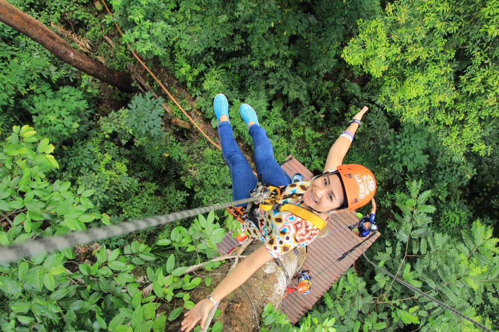 A smiling woman hanging above a forest canopy from a rope.