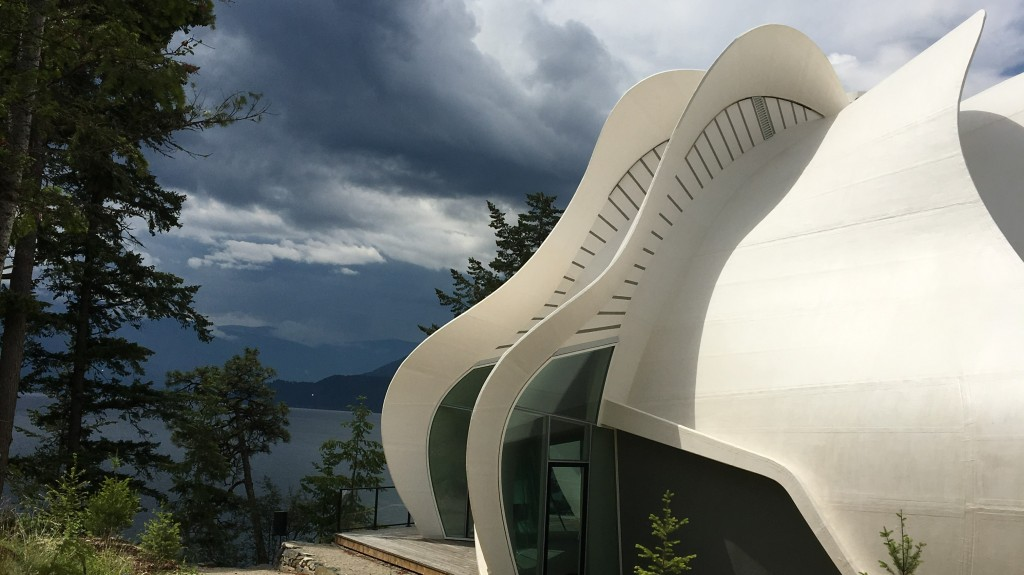 A curved white building against a stormy backdrop of mountains and a lake.