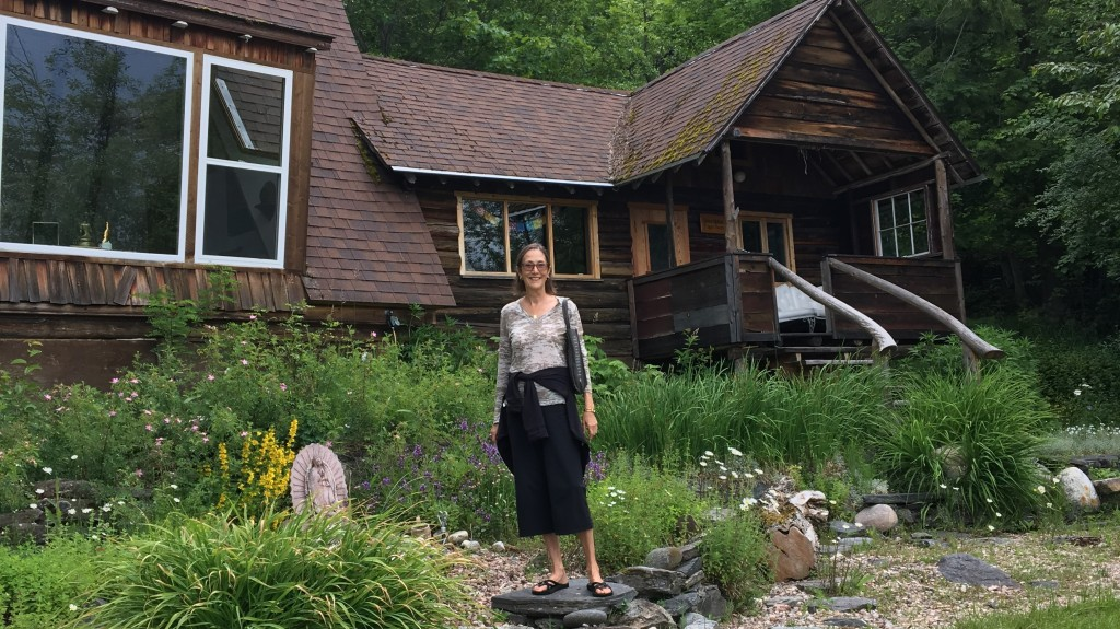 The author stands in a green garden in front of a rustic wooden building.